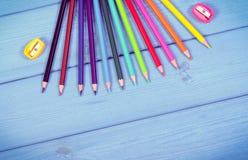Weinlesefoto, bunte Zeichenstifte und Bleistiftspitzer auf blauen Brettern, Schulzubehör, Kopienraum für Text Lizenzfreies Stockfoto