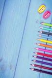Weinlesefoto, bunte Zeichenstifte und Bleistiftspitzer auf Brettern, Schulzubehör, Kopienraum für Text Lizenzfreie Stockfotos
