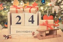 Weinlesefoto, datieren am 24. Dezember auf Kalender, eingewickelte Geschenke und Weihnachtsbaum mit Dekoration, Weihnachtsabends- Stockfotografie