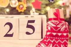 Weinlesefoto, datieren am 25. Dezember auf Kalender, Geschenk in der Socke und Weihnachtsbaum mit Dekoration Lizenzfreies Stockbild