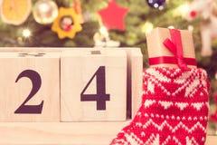 Weinlesefoto, datieren am 24. Dezember auf Kalender, Geschenk in der Socke und Weihnachtsbaum mit Dekoration Lizenzfreie Stockfotografie