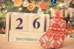 Weinlesefoto, datieren am 26. Dezember auf Kalender, Geschenk in der Socke und Weihnachtsbaum mit Dekoration, Weihnachtszeit Stockfotografie