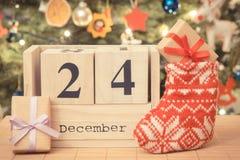 Weinlesefoto, datieren am 24. Dezember auf Kalender, Geschenke mit festlicher Socke und Weihnachtsbaum, Weihnachtsabendszeit Stockbilder