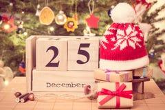 Weinlesefoto, datieren am 25. Dezember, Geschenke mit Schlitten und Kappe, Weihnachtsbaum mit Dekoration, festliches Zeitkonzept Lizenzfreies Stockbild