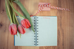 Weinlesefoto, Datum des vom 14. Februar herein Notizbuches, frische Tulpen und eingewickeltes Geschenk, Valentinsgruß-Tag Lizenzfreies Stockfoto