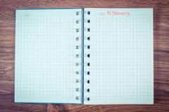 Weinlesefoto, Datum vom 14. Februar geschrieben in Notizbuch, Valentinsgruß-Tag Lizenzfreies Stockbild