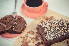 Weinlesefoto, dunkler Kuchen mit Schokolade, Kakao und Pflaume stauen, Tasse Kaffee, Konzept des köstlichen Nachtischs Lizenzfreie Stockbilder