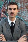 Weinlesefoto eines jungen eleganten klassischen Mannes mit seinen Armen kreuzte im modernen Graffitihintergrund Stockbilder