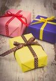 Weinlesefoto, eingewickelte bunte Geschenke für Weihnachten oder andere Feier auf alter weißer Planke Stockbilder