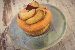 Weinlesefoto, frische gebackene Muffins mit Pflaumen auf Platte auf altem hölzernem Hintergrund, köstlicher Nachtisch Stockbild