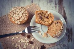 Weinlesefoto, frische Muffins mit Hafermehl backte mit Vollkornmehl auf weißer Platte, köstlicher gesunder Nachtisch Stockbilder