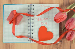 Weinlesefoto, Valentinsgruß-Tag geschrieben in Notizbuch, frische Tulpen, eingewickeltes Geschenk und Herz, Dekoration für Valent Lizenzfreies Stockfoto