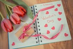 Weinlesefoto, Valentinsgruß-Tag geschrieben in Notizbuch, frische Tulpen, eingewickeltes Geschenk und Herzen, Dekoration für Vale Stockfotos