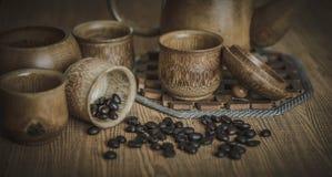 Weinlesefoto von Kaffeebohnen und von Kaffeetassen stellte auf hölzernen Hintergrund ein Stockfotos
