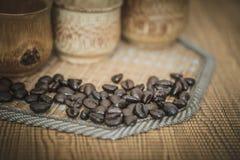 Weinlesefoto von Kaffeebohnen und von Kaffeetassen stellte auf hölzernen Hintergrund ein Lizenzfreie Stockbilder