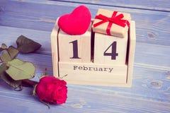 Weinlesefoto, Würfelkalender mit Geschenk, rotes Herz und rosafarbene Blume, Valentinsgrußtag Lizenzfreie Stockfotos