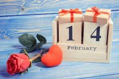 Weinlesefoto, Würfelkalender mit Geschenk, rotes Herz und rosafarbene Blume, Valentinsgrußtag Lizenzfreies Stockbild