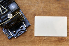 Weinlesefotokamera mit leerem Fotorahmen auf einem Holztisch Lizenzfreies Stockbild