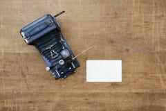 Weinlesefotokamera mit leerem Fotorahmen auf einem Holztisch Stockfoto