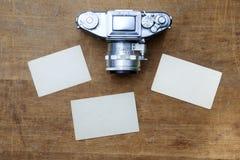 Weinlesefotokamera mit leerem Fotorahmen auf einem Holztisch Lizenzfreie Stockbilder