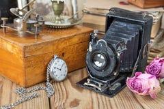 Weinlesefotokamera, Taschenuhren und getrocknete Rosen Stockbild