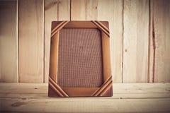 Weinlesefotorahmen auf Holztisch über hölzernem Hintergrund Stockfotos