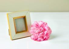 Weinlesefotorahmen und rosa Gartennelke blühen auf Holztisch Stockfotografie