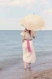 Weinlesefrau auf Strand mit Sonnenschirm Lizenzfreies Stockbild