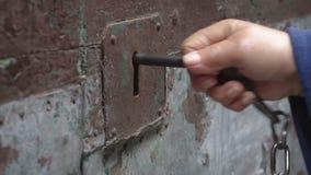 Weinlesefrau, die eine alte Tür mit einer alten Schlüsselzeitlupe MF öffnet stock video