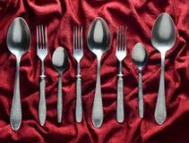 Weinlesegabeln und -löffel auf einer roten silk Tischdecke Beschneidungspfad eingeschlossen Stockbilder