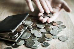 Weinlesegeldbeutel voll alte Münzen mit den Händen im Hintergrund Lizenzfreie Stockfotografie