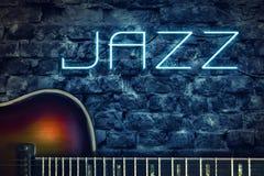Weinlesegitarre und ein Neonaufschrift Jazz auf dem Hintergrund einer alten Backsteinmauer Konzeptmusik lizenzfreies stockbild