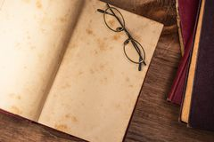 Weinlesegläser auf offenem altem Buch Stockbild