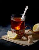 Weinleseglashalter auf gestrickter Serviette mit Tasse Tee mit geschnittenen Zitronen- und Zuckerwürfeln über alter Metalltabelle Lizenzfreie Stockfotos