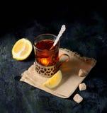 Weinleseglashalter auf gestrickter Serviette mit Tasse Tee mit geschnittenen Zitronen- und Zuckerwürfeln über alter Metalltabelle Lizenzfreie Stockfotografie