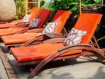 Weinlesehölzernes sunbed mit orange Auflage und Kissen nahe dem Garten am sonnigen Tag lizenzfreies stockfoto