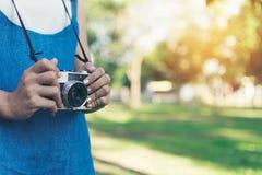 Weinleseherbstfoto mit dem Mädchen, das in einem Park mit alter Kamera steht Stockfotografie