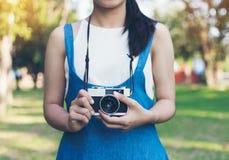 Weinleseherbstfoto mit dem Mädchen, das in einem Park mit alter Kamera steht Stockbilder