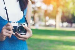Weinleseherbstfoto mit dem Mädchen, das in einem Park mit alter Kamera steht Lizenzfreies Stockbild