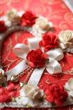 Weinleseherzen von der rosafarbenen Blume auf rotem Papierhintergrund Lizenzfreies Stockfoto