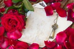 Weinlesehintergrund mit den rosafarbenen Blumenblättern und Schlüssel Lizenzfreie Stockfotografie