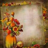 Weinlesehintergrund mit einem Blumenstrauß des Herbstlaubs und der Beeren in einem Vase vom Kürbis Stockfotografie