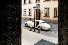 Weinlesehochzeitsauto verziert mit Blumen nahe der Kirche Lizenzfreies Stockbild