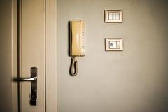 Weinlesehotelzimmeranlagen Alte Schalter und antikes Telefon auf der weißen Wand lizenzfreies stockfoto