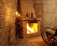 Weinleseinnenraum mit Schaukelstuhl durch Kamin und Kerzen Stockbild