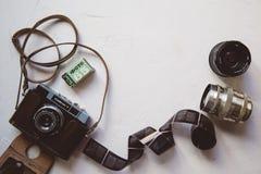 Weinlesekamera, Film, Retro- Linsen auf weißer Tabelle, Kopienraum lizenzfreie stockbilder