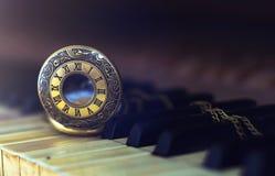 Weinleseklavierschlüssel mit antiker Taschenuhr setzen Zeit Konzeptes fest Stockfoto