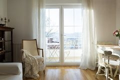 Weinleselehnsessel gegen wei?e Wand und gro?es Fenster mit Vorhang stockbilder
