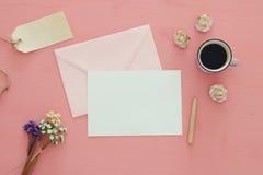 Weinlesemodell mit Blumen, Tasse Kaffee und leerem Buchstaben stockbild