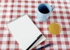 Weinlesenotizbuch mit einer Schale und einer Frucht auf dem Tisch, die warten Stockfotos